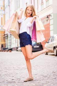 Einkaufen macht glücklich! volle länge der attraktiven jungen fröhlichen frau, die einkaufstaschen hält und die kamera anschaut, während sie im freien steht
