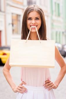 Einkaufen macht spaß! schöne junge frau, die einkaufstasche mit den zähnen trägt und lächelt
