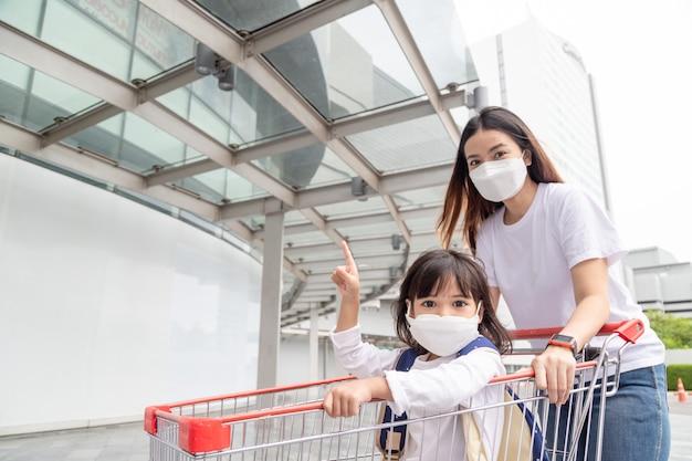Einkaufen mit kindern während eines virusausbruchs asiatische mutter und tochter mit chirurgischer gesichtsmaske