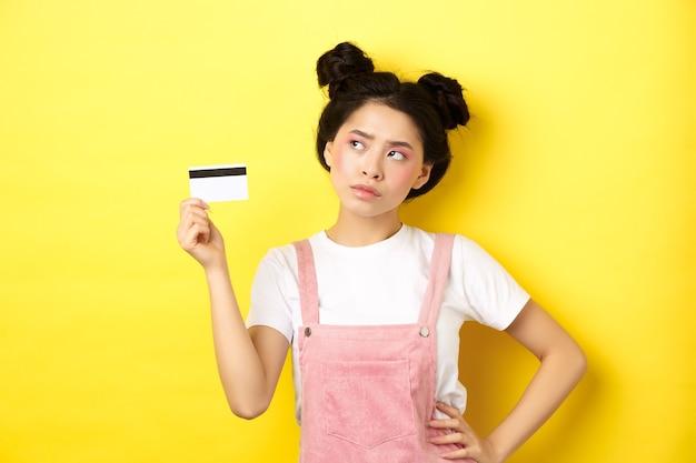 Einkaufen. nachdenkliche asiatische frau mit glamour-make-up, plastik-kreditkarte haltend und nachdenklich beiseite schauend, entscheidung treffen, gelb