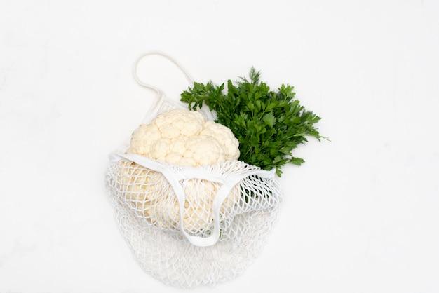 Einkaufen ohne lebensmittelverschwendung. öko-naturbeutel mit obst und gemüse im beutel, umweltfreundlich, flach gelagert.