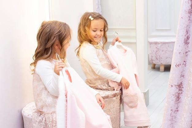 Einkaufen. rabatte. kleines mädchen shopaholic. mädchen probiert ein schönes kleid an, das in der umkleidekabine der boutique sanft rosa ist. einkaufszentrum, einkaufen. emotionen