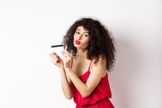 Einkaufen. schöne dame mit lockigem haar, fältchenlippen, küssende plastikkreditkarte, im roten kleid gegen weißen hintergrund stehend.