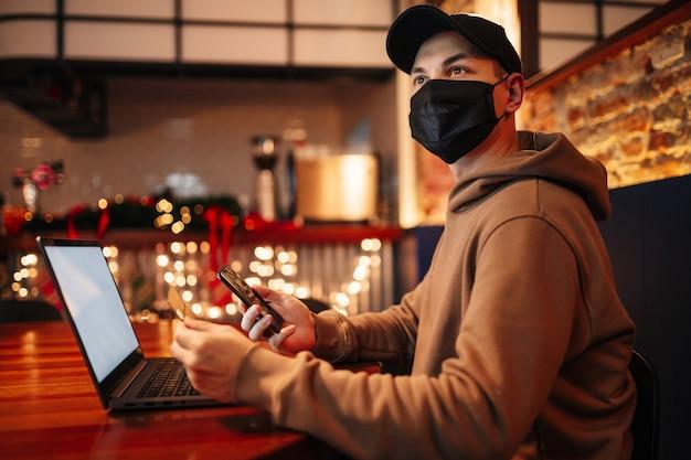 Einkaufen und online-zahlung mit handy, laptop und kreditkarte. mann, der maske während der pandemie trägt