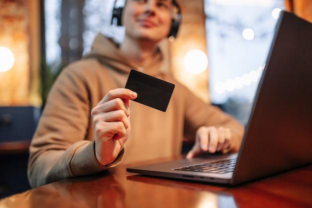 Einkaufen und online-zahlung mit laptop und kreditkarte. mann, der in einem café sitzt, das freizeitkleidung trägt, kauft waren und zahlt über internet mit einer schwarzen debitkarte. neues normal- und technologiekonzept.
