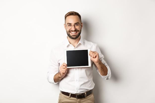 Einkaufen und technik. hübscher mann, der digitalen tablettbildschirm zeigt, brille mit weißem kragenhemd, studiohintergrund tragend.