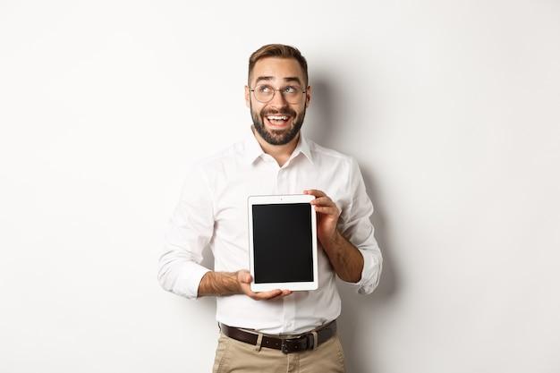 Einkaufen und technik. nachdenklicher mann, der digitalen tablettbildschirm zeigt, die obere linke ecke betrachtet und denkt, über weißem hintergrund stehend.