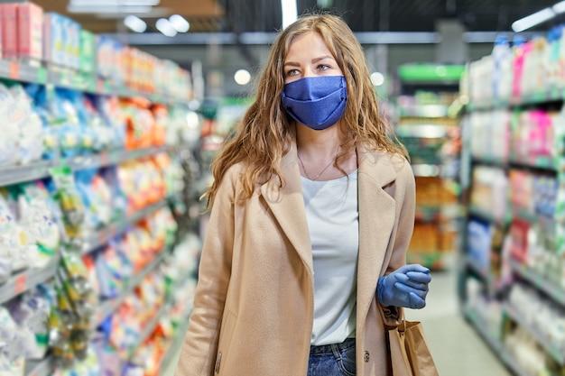Einkaufen während der covid-19-pandemie. frau in gesichtsmaske kauft lebensmittel im supermarkt.