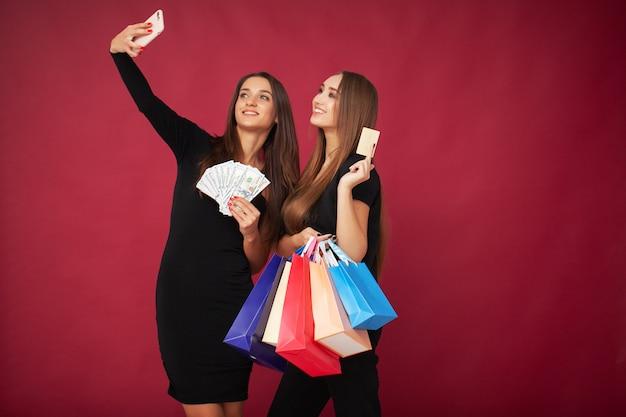 Einkaufen. zwei frauen, die farbige taschen in schwarzem freitag halten