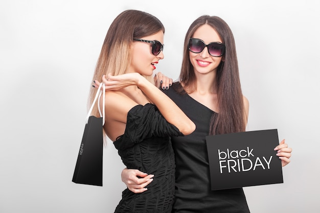 Einkaufen. zwei frauen, die schwarze taschen auf hellem hintergrund in schwarzem freitag-feiertag halten