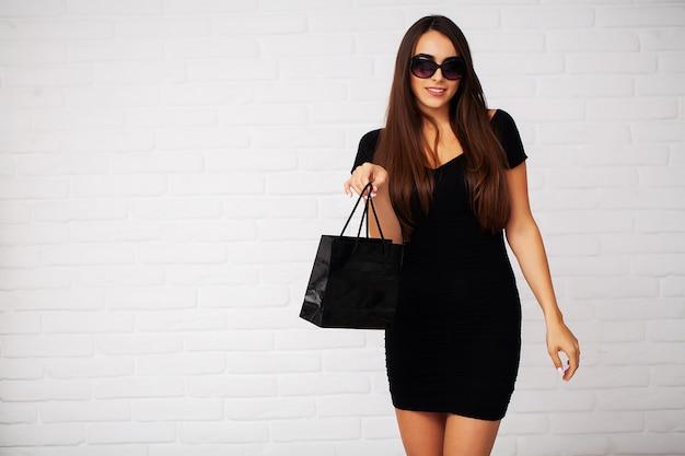 Einkaufende frau, die schwarze tasche im schwarzen freitagurlaub hält