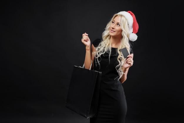 Einkaufende frau in der weihnachtsmannmütze, die tasche auf dunkler wand in den weihnachtsferien hält. verkaufskonzept