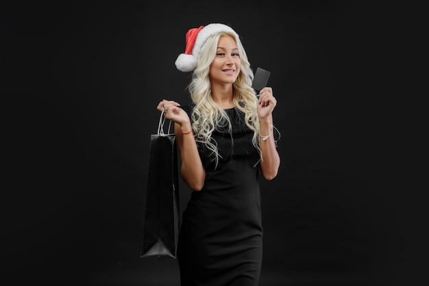 Einkaufende frau in der weihnachtsmütze, die tasche ion dunkle wand in den weihnachtsferien hält. schwarzer freitag sale konzept