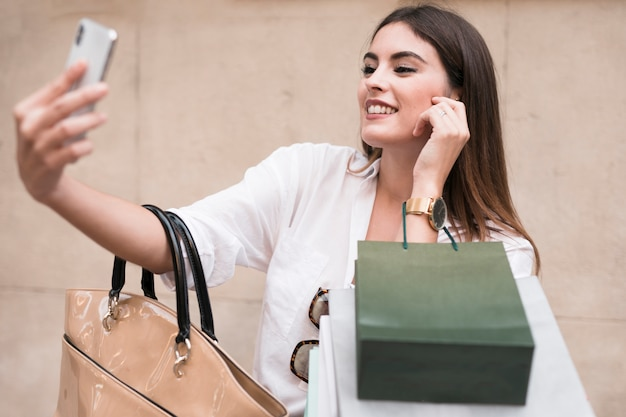 Einkaufenmädchen, das ein selfie nimmt