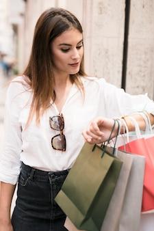 Einkaufenmädchen, das ihre uhr betrachtet