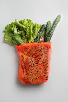 Einkaufennetztasche mit grüns und gemüse.