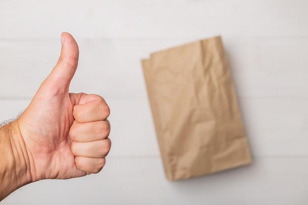 Einkaufpapiertüte und männliche hand, die daumen aufgeben