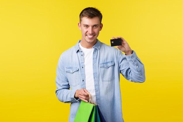 Einkaufs-, freizeit- und rabattkonzept. lächelnder gutaussehender junger mann, der neue kleidung kauft, taschen hält und kreditkarte mit zufriedenem ausdruck zeigt, mit gespartem geld bezahlt, gelber hintergrund.