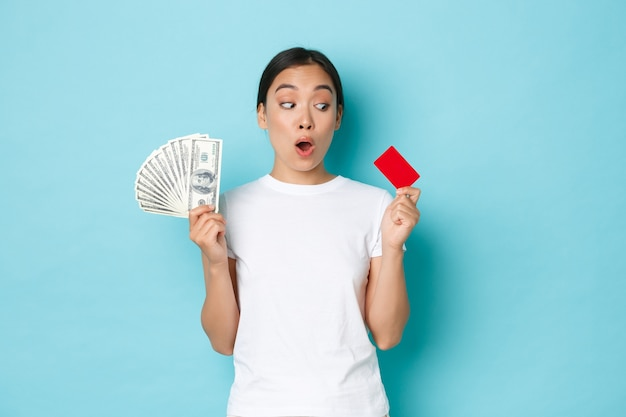 Einkaufs-, geld- und finanzkonzept. erstauntes schönes asiatisches mädchen im weißen t-shirt, das erstaunt nach luft schnappt und kreditkarte betrachtet, während bargeld in der anderen hand hält, bevorzugen kontaktloses bezahlen.