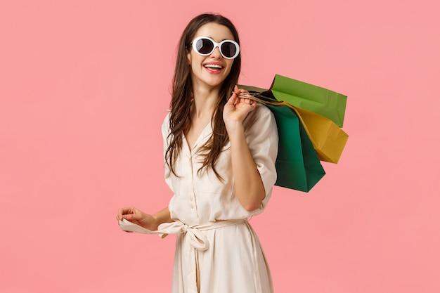 Einkaufs-, lebensstil- und verbraucherkonzept. attraktives junges sorgloses mädchen in den gläsern und im kleid, schauen mit erfülltem lächeln nach dem guten einkauf zurück und stehen rosa wand