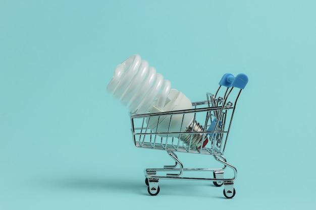 Einkaufs-öko-konzept einkaufswagen mit spiralförmiger glühbirne