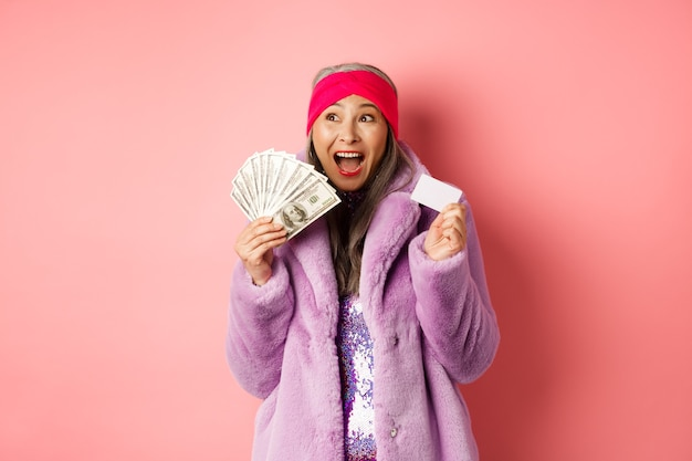 Einkaufs- und modekonzept. asiatische seniorin schreit glücklich wie gewinnerin, hält dollargeld und plastikkreditkarte, sieht aufgeregt aus, rosa hintergrund