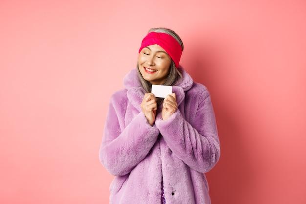 Einkaufs- und modekonzept. modische asiatische frau in lila kunstpelzmantel, glücklich aussehend und plastikkreditkarte zeigend, fröhlich lächelnd, auf rosafarbenem hintergrund stehend