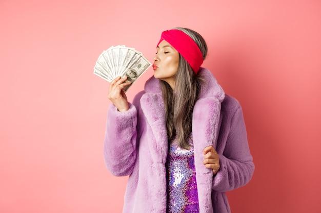 Einkaufs- und modekonzept. modische und reiche seniorin, die dollargeld küsst, zufrieden aussieht, lila kunstpelzmantel mit partykleid trägt, rosa hintergrund