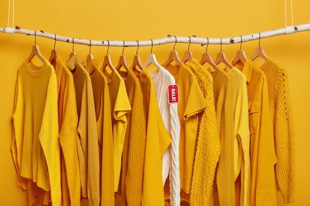 Einkaufs- und sonderangebotskonzept. viele gelbe kleidungsstücke und weißer strickpullover mit rotem etikettenverkauf.