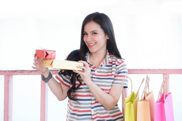 Einkaufsfeiertag der jungen frau / glücklicher smiley des schönen asiatischen mädchens und griffgeschenkbox und einkaufstasche draußen für weihnachten und festival oder valentinstag des neuen jahres