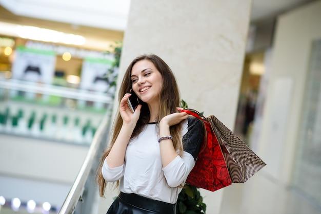 Einkaufsfrau, die am telefon in einem einkaufszentrum spricht