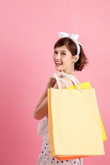 Einkaufsfrau, die einkaufstaschen auf rosa hält
