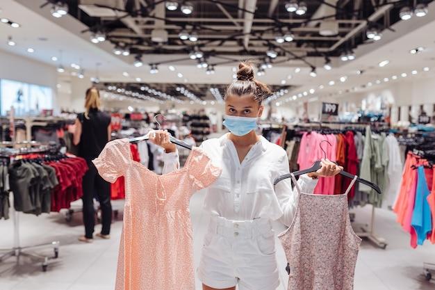 Einkaufskleidung der jungen frau in der kleidungsboutique mit schützender gesichtsmaske