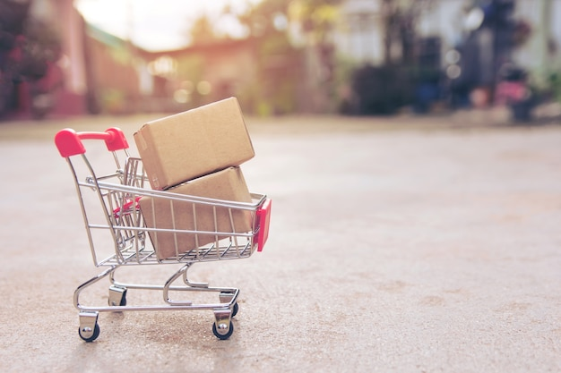 Einkaufskonzept: kartons oder papierkästen im einkaufswagen auf konkretem boden. mit kopie sp