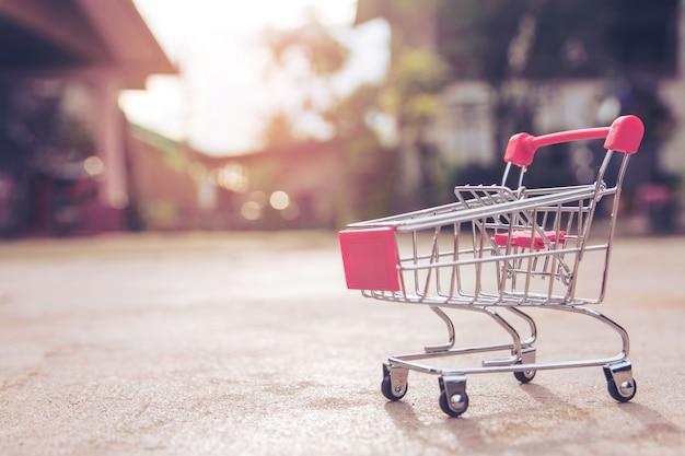 Einkaufskonzept: kleines rotes leeres warenkorbspielzeug auf konkretem boden. supermark einkaufen