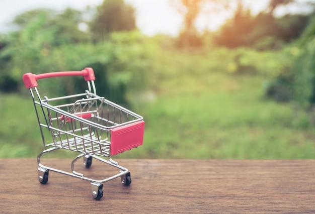 Einkaufskonzept: leerer warenkorb auf brauner hölzerner tabelle.