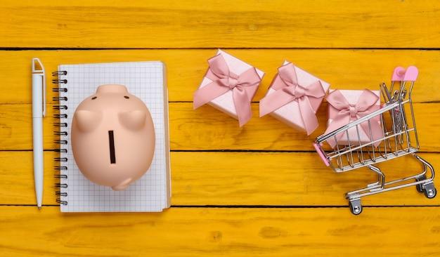 Einkaufskonzept, wirtschaftlichkeit, einkaufsliste. sparschwein mit supermarktwagen, geschenkboxen, notizbuch auf gelber holzoberfläche. draufsicht