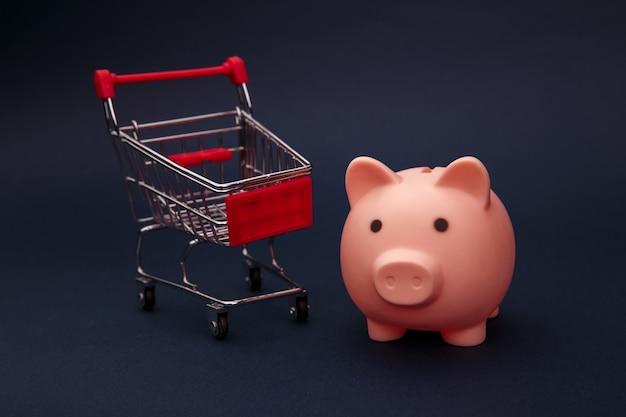 Einkaufskonzept, wirtschaftlichkeit. sparschwein mit supermarktwagen