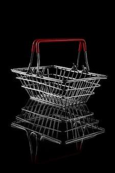 Einkaufskorb aus stahldraht für lebensmittel auf dunklem hintergrund mit kopierraum. konzept des black friday-verkaufs