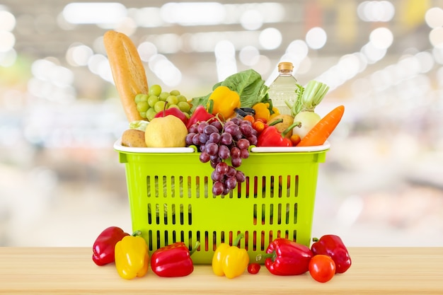 Einkaufskorb gefüllt mit obst und gemüse auf holztisch mit supermarkt lebensmittelgeschäft verschwommen defokussiert