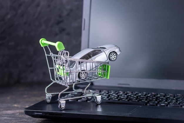 Einkaufskorb mit auto auf laptoptastatur auf dunklem hintergrund