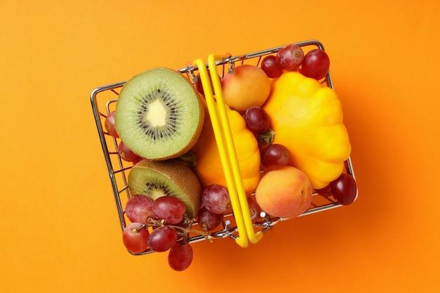 Einkaufskorb mit gemüse und obst auf orangem hintergrund