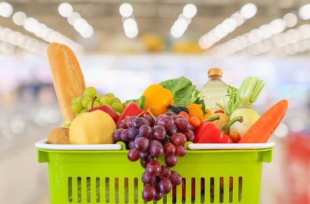Einkaufskorb mit lebensmittelgeschäfthintergrund