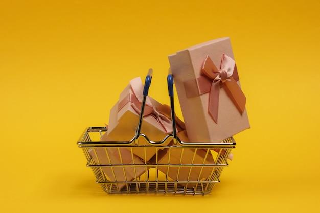 Einkaufskorb und geschenkboxen mit schleifen auf gelbem hintergrund. komposition für weihnachten, geburtstag oder hochzeit.
