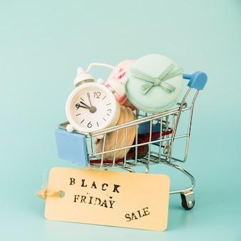 Einkaufslaufkatze mit wecker und makronen nähern sich verkaufstag