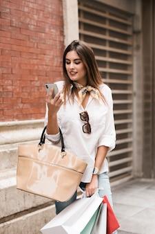 Einkaufsmädchen, das ihren handy betrachtet