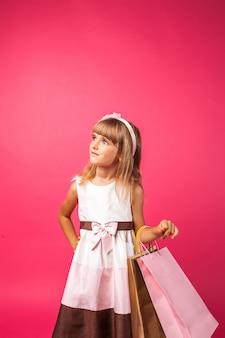 Einkaufsmädchen, das papiereinkaufstüten auf rosa wand hält