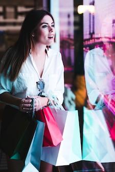 Einkaufsmädchen, das schaufenster betrachtet