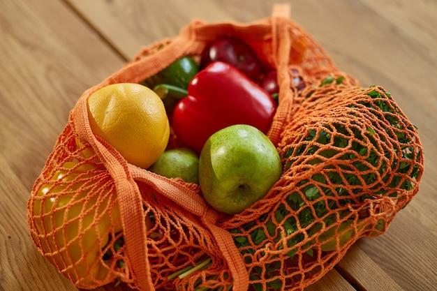 Einkaufsnetz-ökotasche mit gesundem veganem gemüse und obst in der küche zu hause, vegetarisches konzept für gesunde ernährung.
