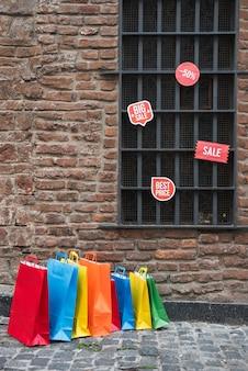 Einkaufspakete und verkaufstabletten nähern sich fenster auf backsteinmauer